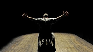 Uomo in sedia a rotelle sul palco di un teatro