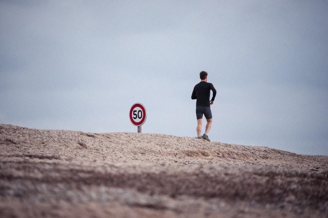 cinquant'anni: jogger e cartello con limite di velocità