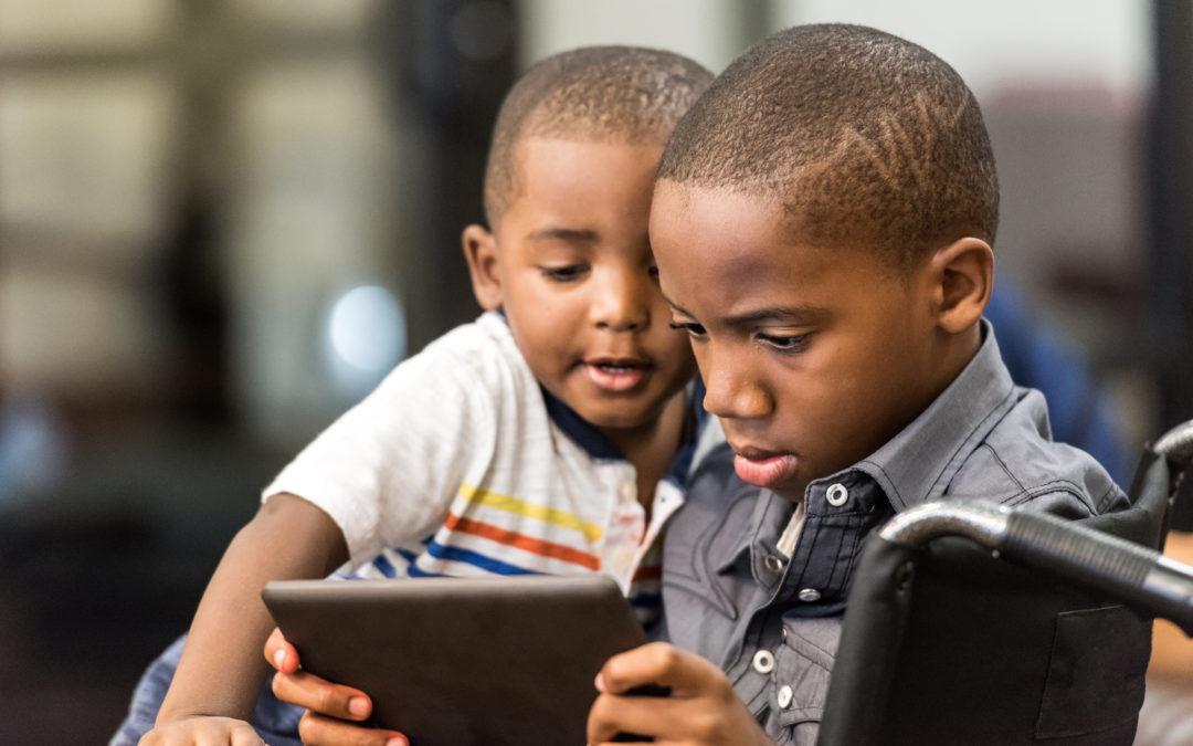 Due bambini immigrati guardano un tablet: immagine di migrazione digitale