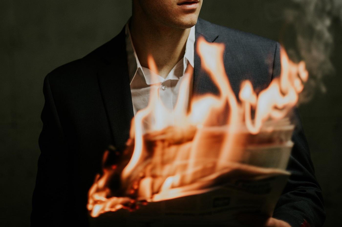 Un uomo guarda un giornale che va a fuoco: il mestiere di giornalista a rischio