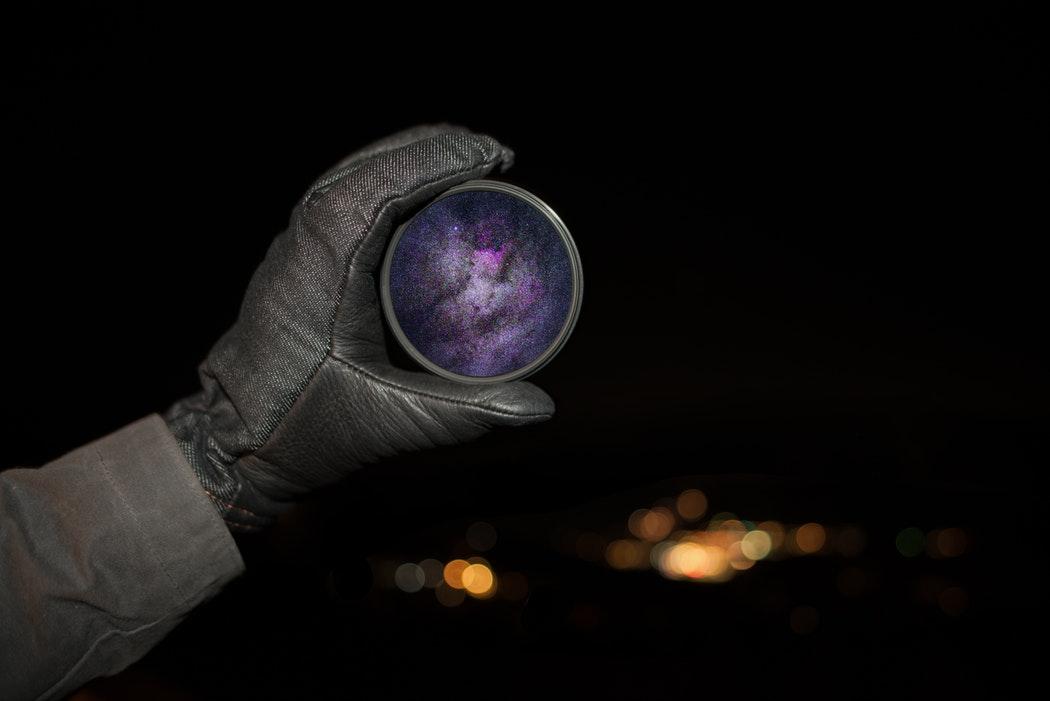 Modelli vs esperienza per capire la natura: una mano regge un universo come una lente