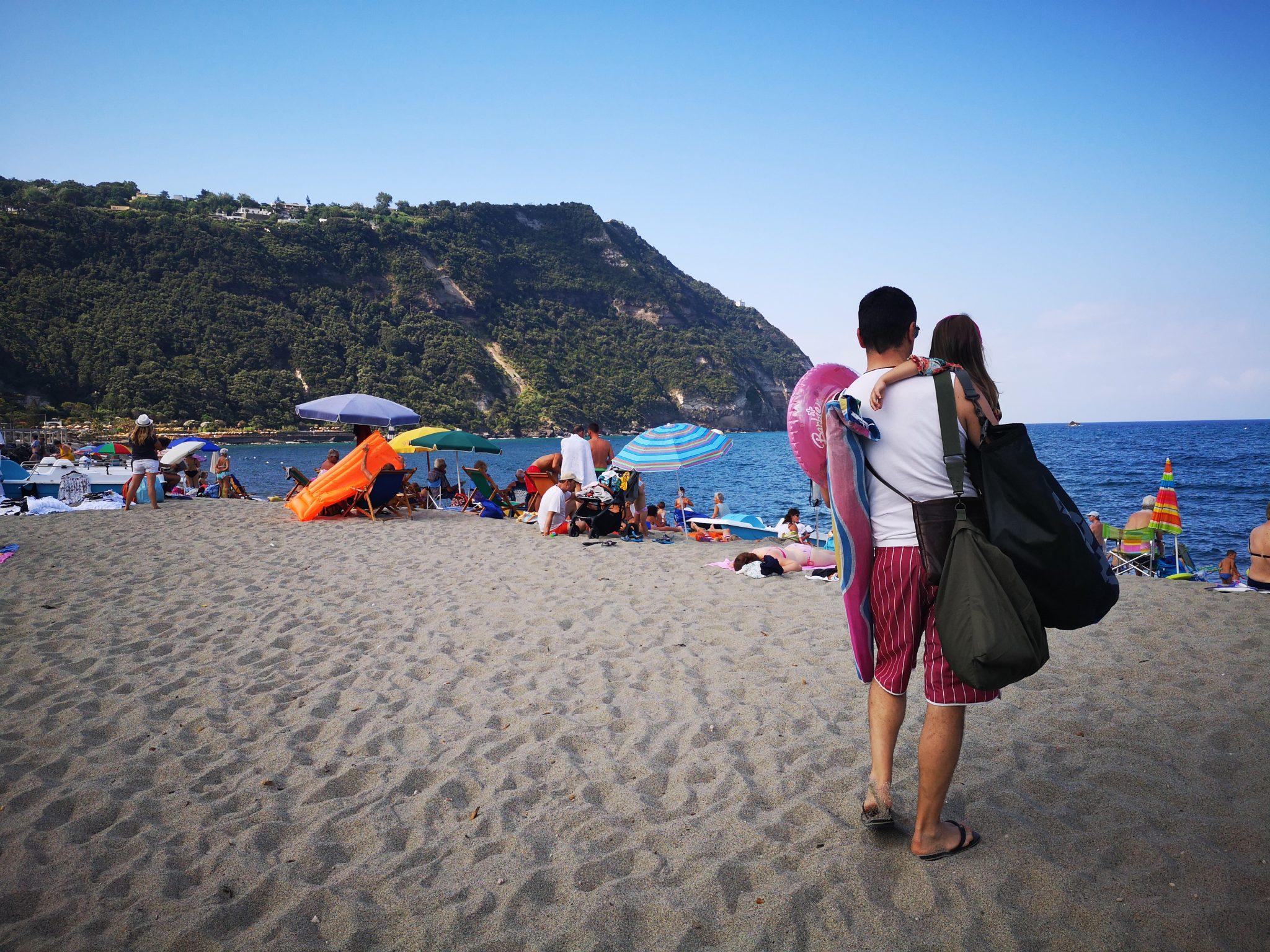 L'estate dei genitori: un papà sulla spiaggia con la figlia in braccio