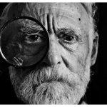Un uomo anziano con una lente d'ingrandimento, che simboleggia l'istruzione