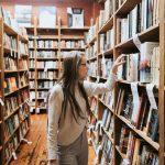 Studiare non basta mai: una donna sceglie un libro in biblioteca