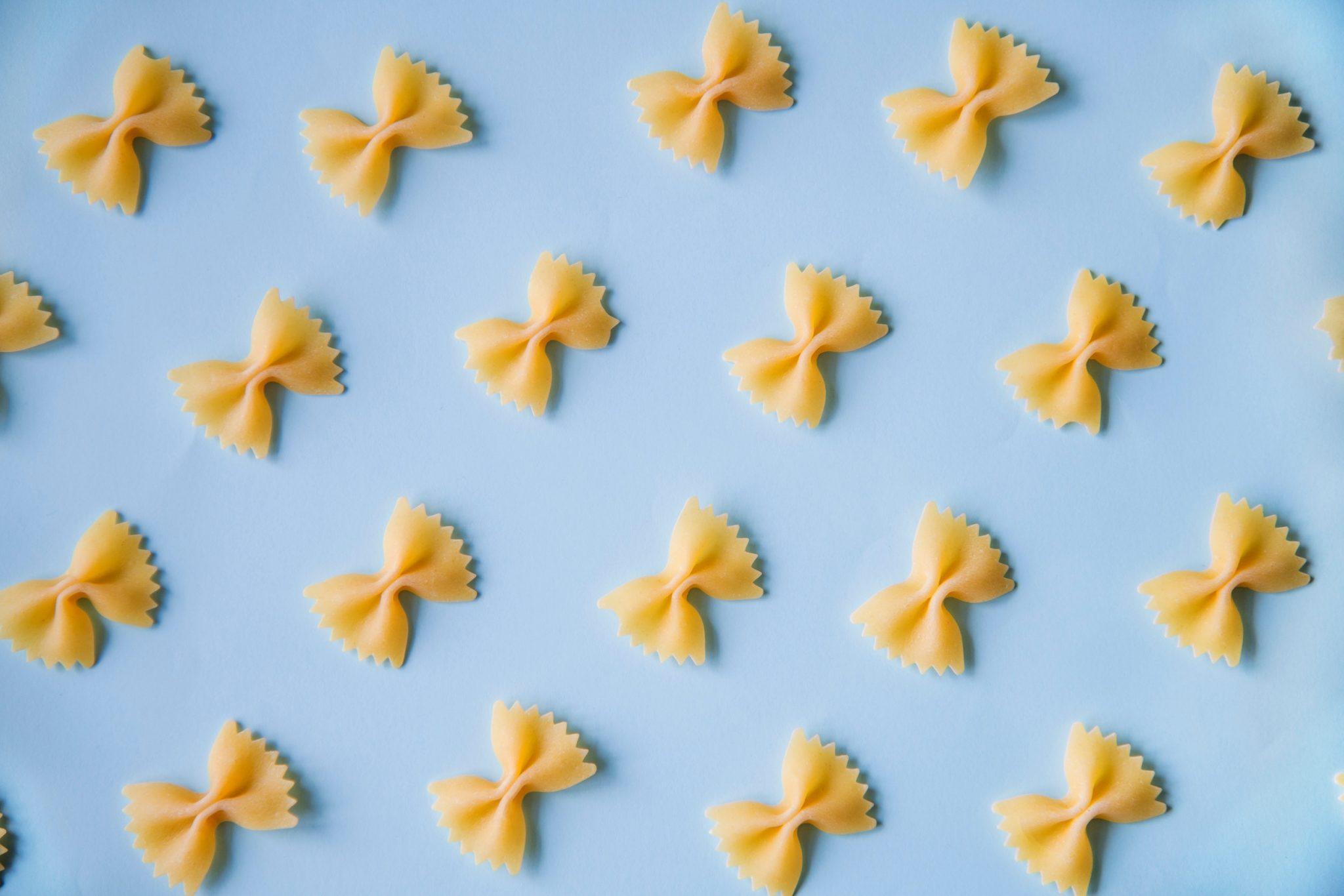 Farfalle (pasta) su sfondo azzurro cielo: simbolo della fuga dei cervelli italiani
