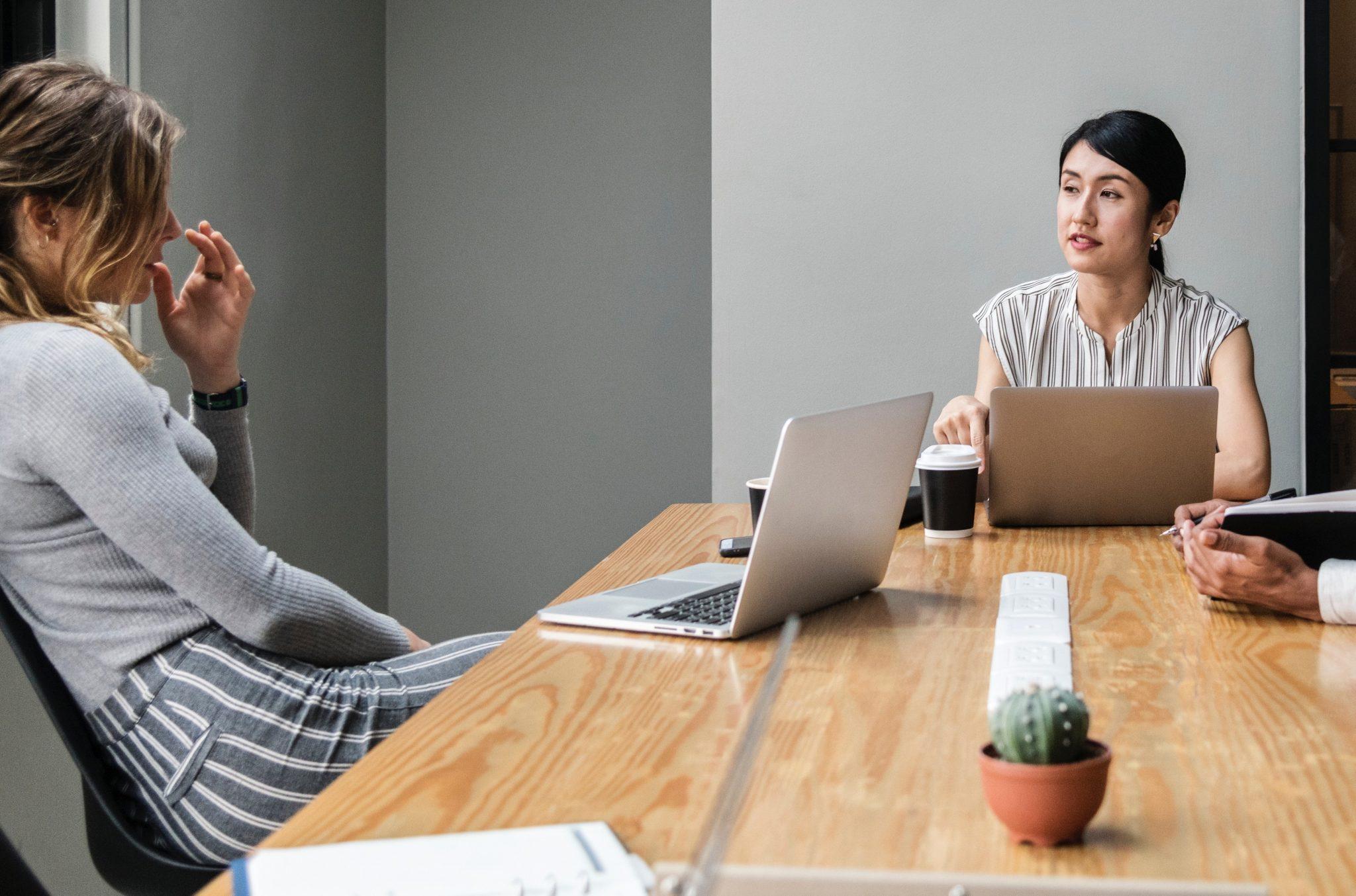 Due donne che conversano in ufficio: rimanere umani sul lavoro non è sempre facile.