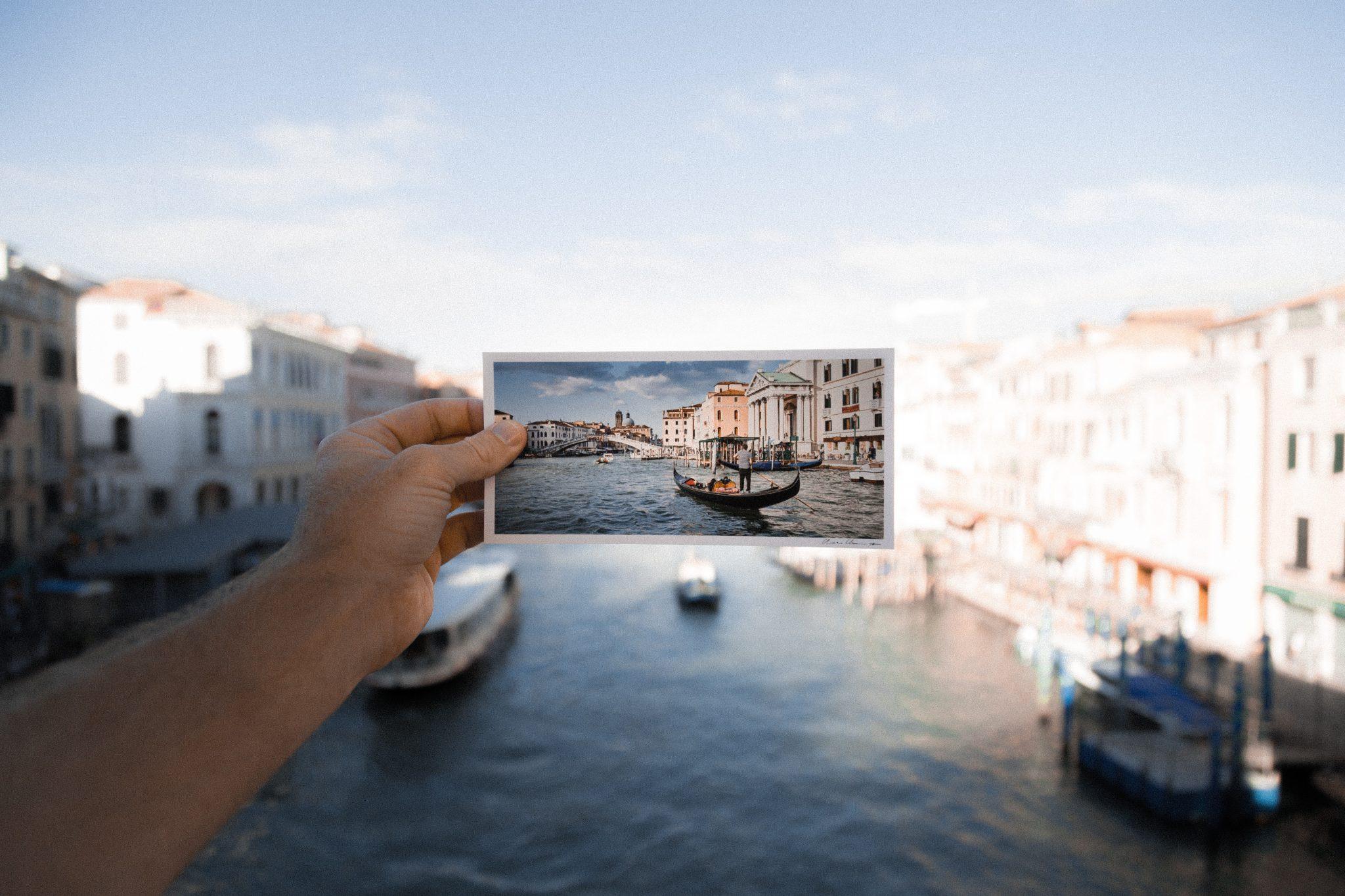 Una cartolina di Venezia contro il reale paesaggio della città, metafora del turismo veneto