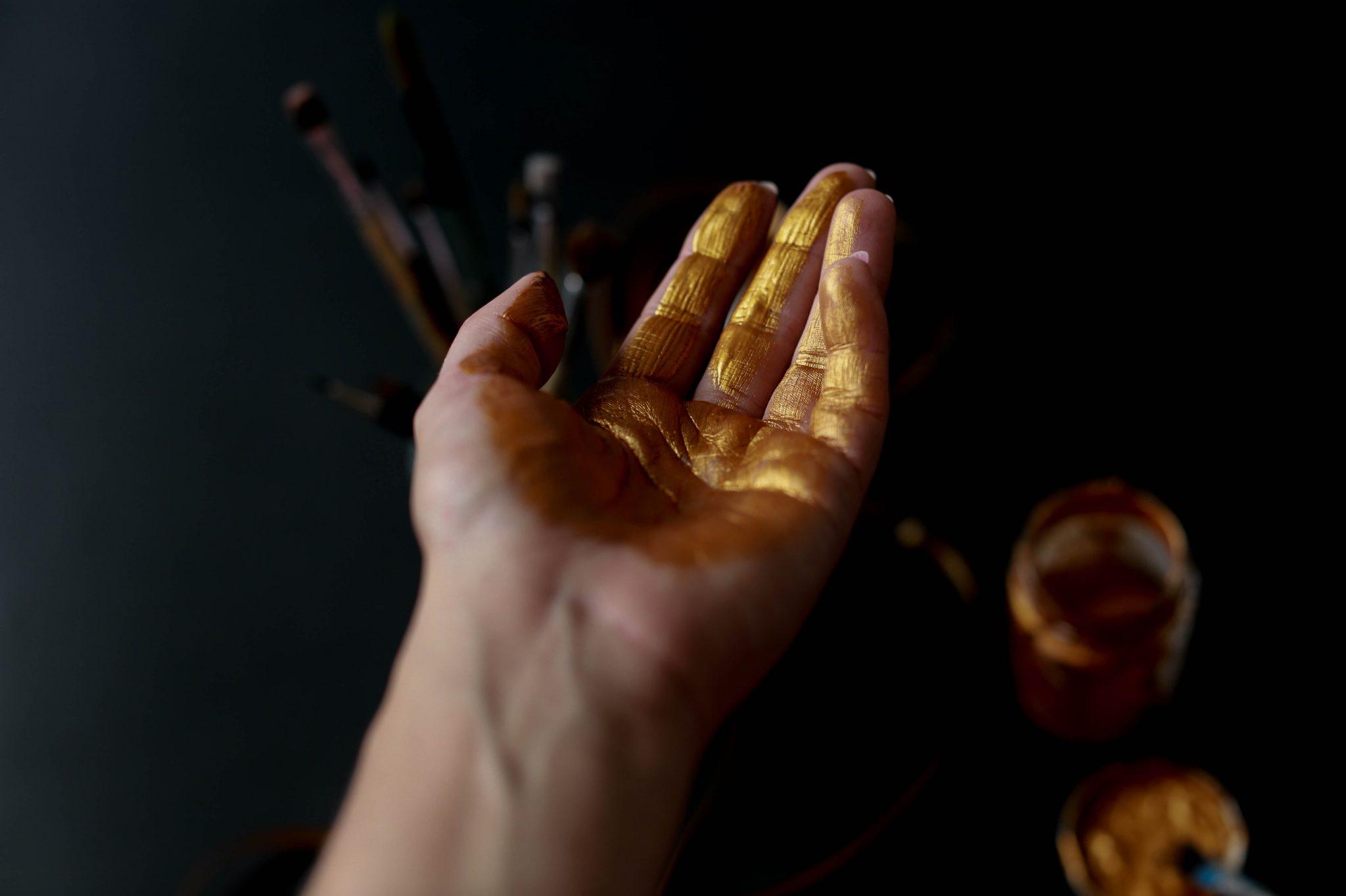 Una mano patinata in oro.