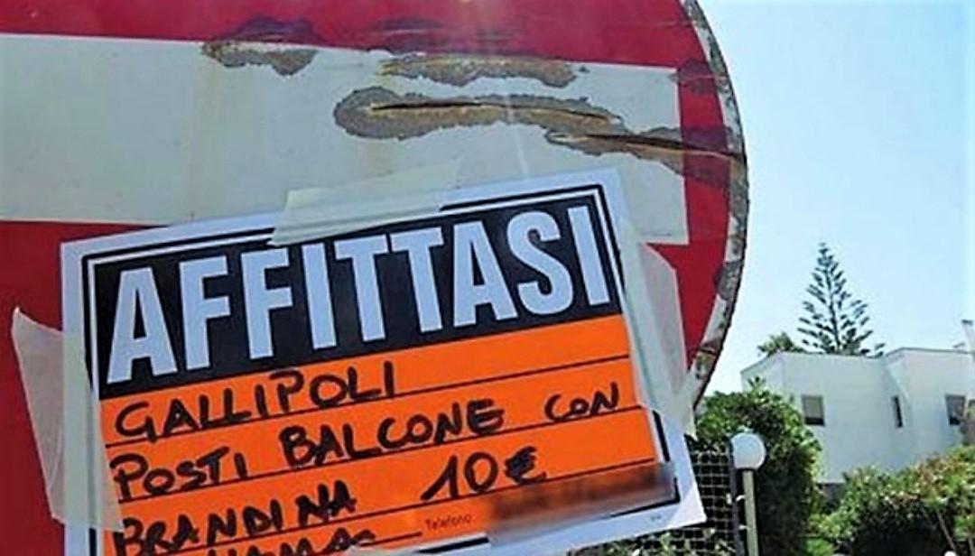 Un cartello per affittare un balcone a Gallipoli, simbolo dell'abusivismo nel turismo in Puglia
