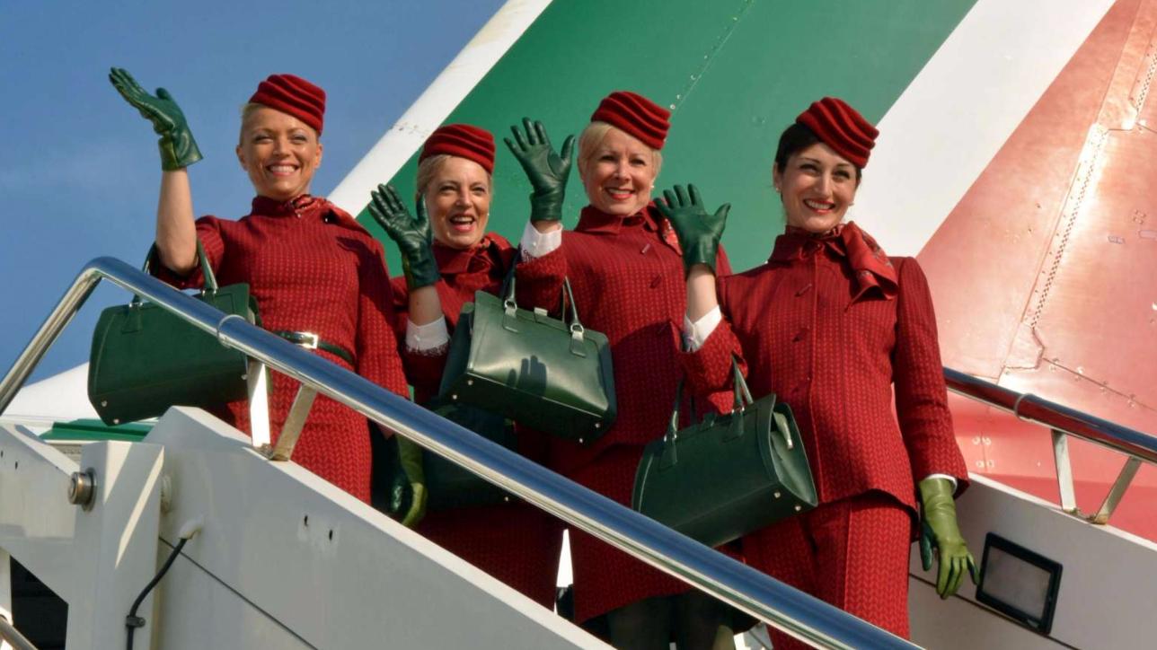 Salvare Alitalia: delle hostess della compagnia di bandiera salutano dall'ingresso di un aereo.