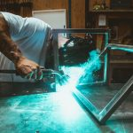 Operaio in imprese industriali salda cornici di metallo