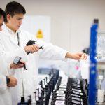 Due studenti col camice in un laboratorio chimico, incontro tra università e manifattura