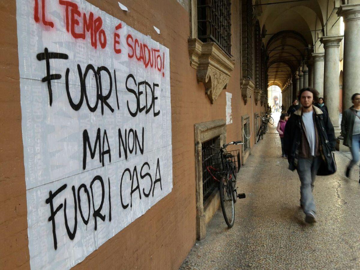 """Un cartello di un'associazione studentesca appeso su un muro di Bologna """"la dotta"""""""