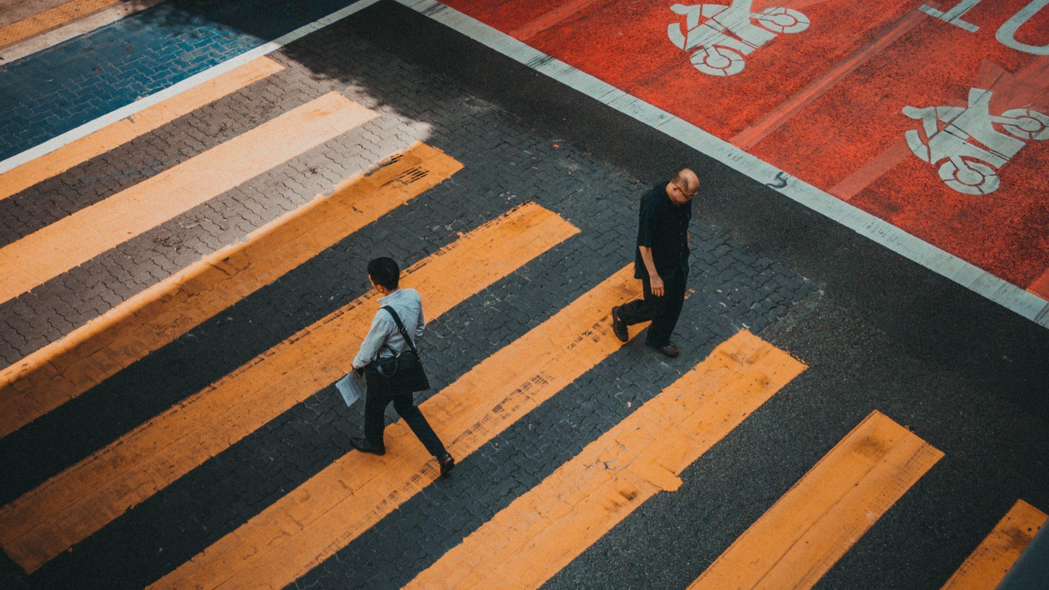 Metafora della diversità in azienda: due persone che si incrociano sulle strisce pedonali senza guardarsi.