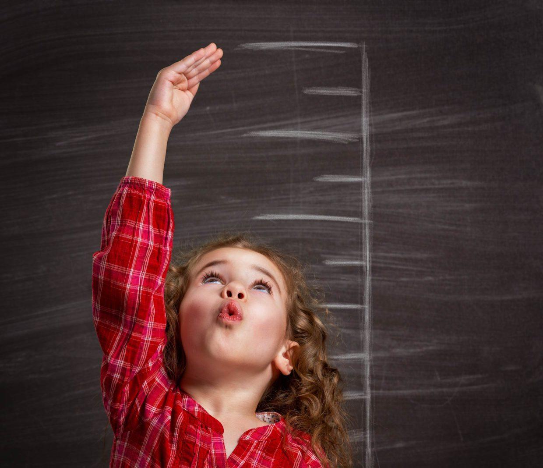 Italia a crescita zero: una bambina che si misura con un metro disegnato sul muro