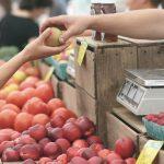 Uno scambio di frutta dal venditore al cliente: un punto basilare per capire le relazioni che orientano la bussola del mercato.