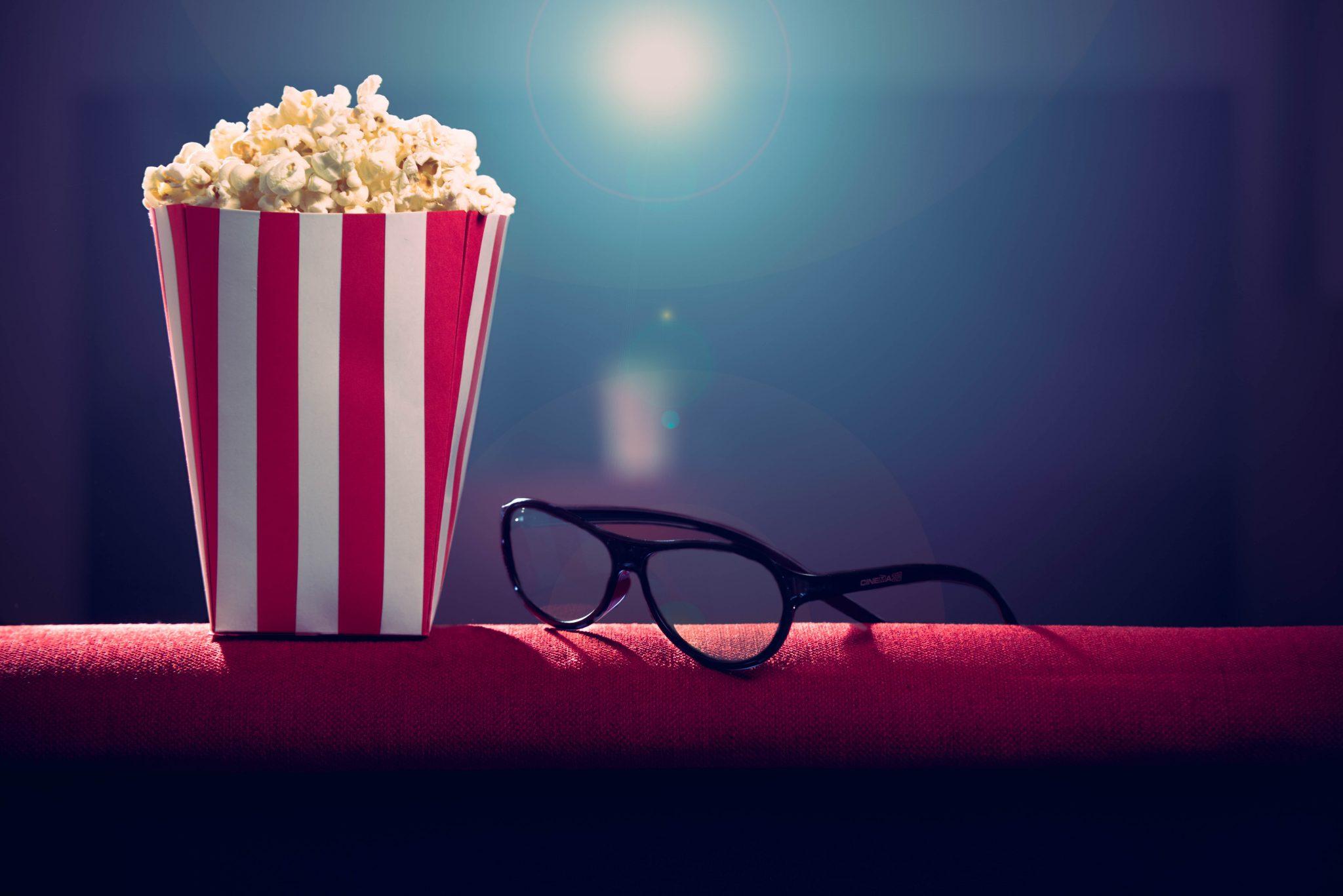 Popcorn e occhiali in una sala cinematografica: nel settore si prepara una guerra a Netflix.