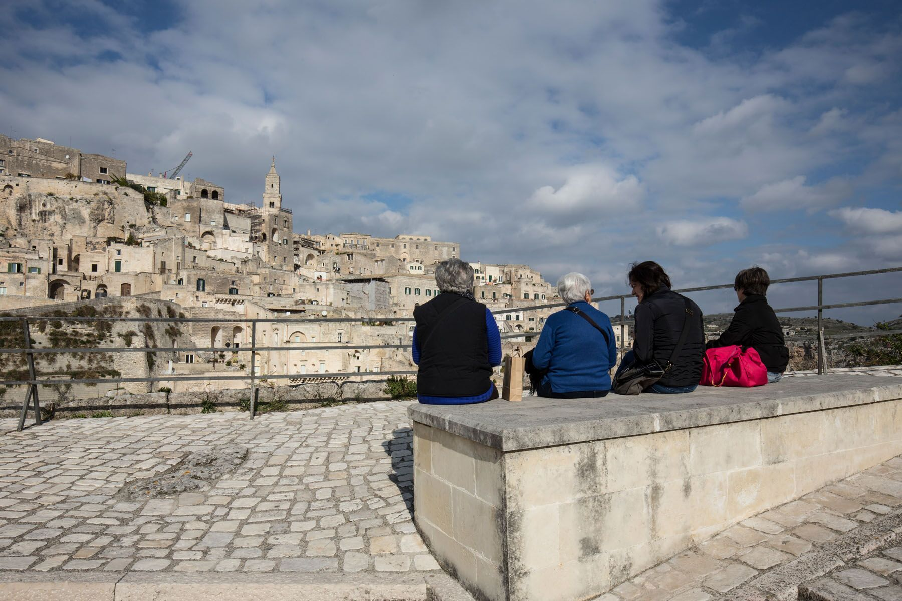 Essere di Matera: anziani su una panchina di pietra che osservano la città