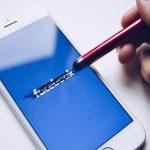 Facebook annuncia Libra, la sua criptovaluta: nell'immagine, una penna cancella il nome dell'azienda su uno schermo digitale