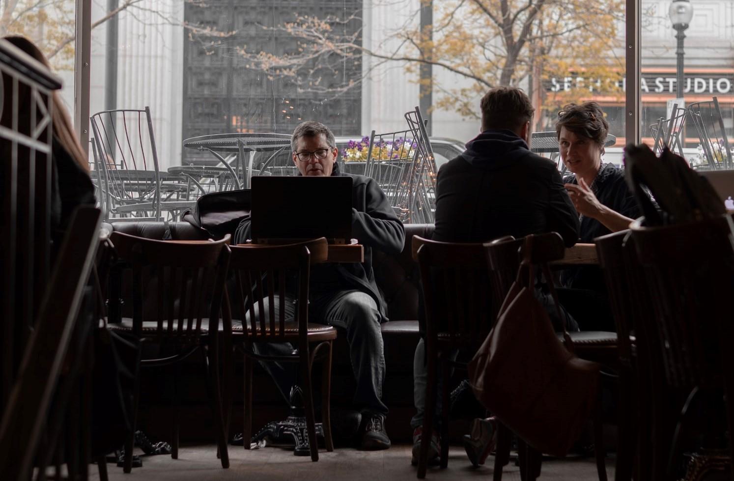 La solitudine del consulente: un uomo da solo davanti a un laptop a un tavolo di ristorante