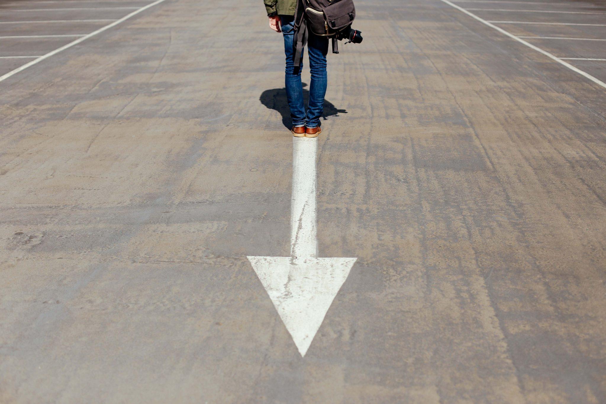 Metafora del purpose: una freccia che indica a una persona la direzione in cui muoversi su una pista.
