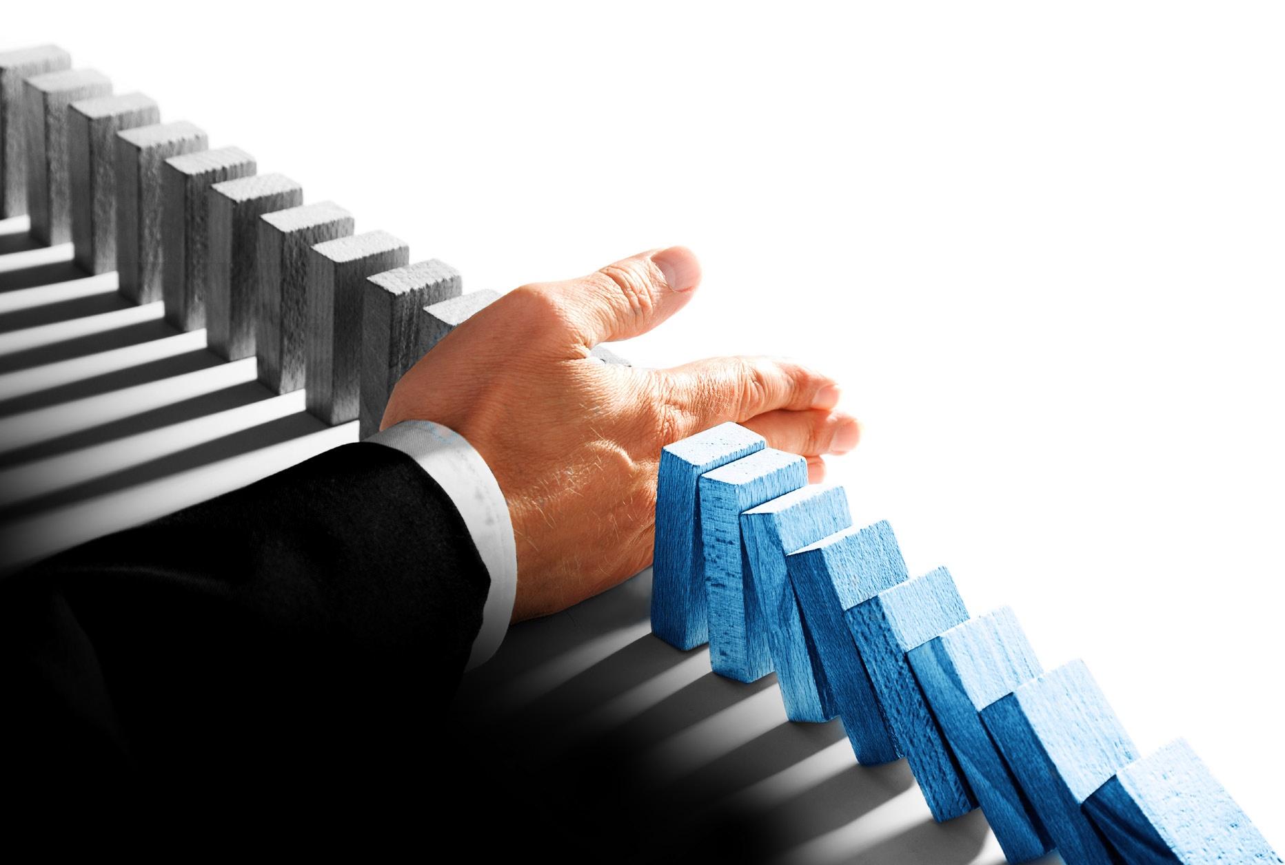 Mediazione aziendale: una mano ferma la caduta delle tessere del domino