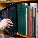 """Un """"libro digitale"""": un tablet estratto da uno scaffale di testi"""