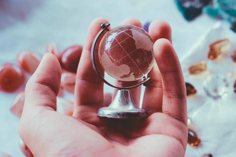 Lavoro in provincia: un globo in palmo di mano, come l'internazionalizzazione che potrebbe spingere sempre più verso il lavoro decentralizzato.