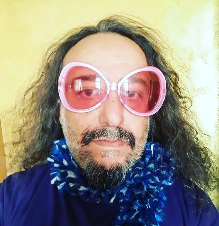 Una foto di Michele Monina con degli occhiali rosa.
