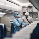Addetti alle pulizie in tuta sanitaria all'opera su un aereo.