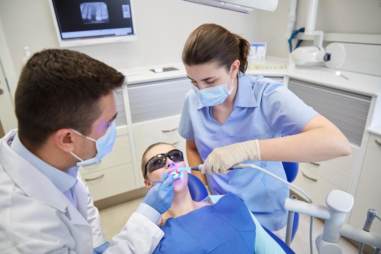 Dei dentisti al lavoro su una paziente.