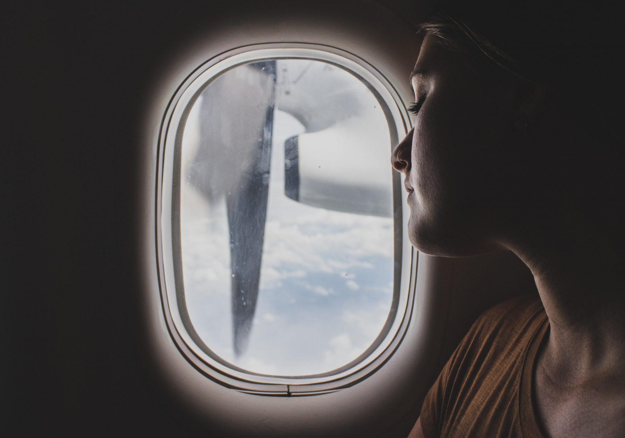 Una delle donne expat guarda fuori dal finestrino dell'aereo.
