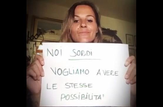 """Sara Giada Gerini, la """"Giovanna D'Arco dei sordi"""", con un cartello che recita: """"Noi sordi vogliamo avere le stesse possibilità""""."""