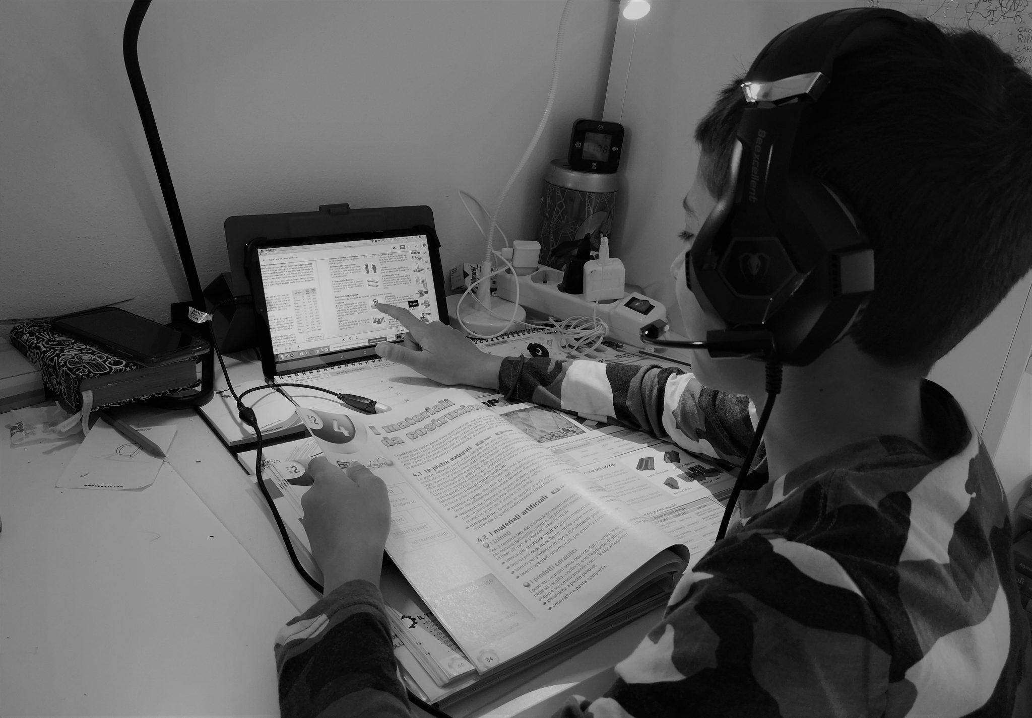 Tutti promossi gli studenti italiani costretti alla didattica a distanza; come quello in foto, che studia da libro e tablet.