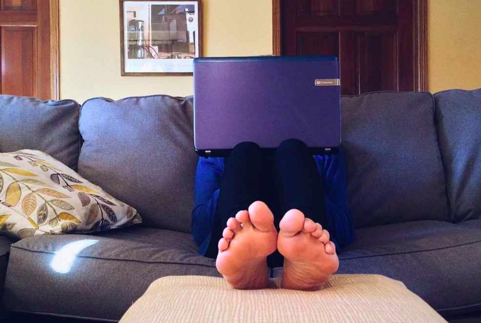 Rivoluzione coronavirus: un uomo lavora al portatile da casa, sul divano, a piedi nudi.