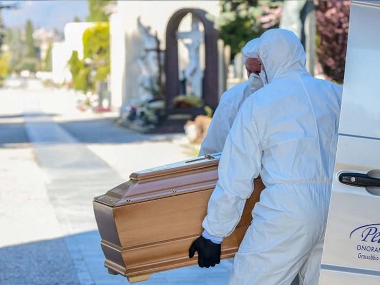 Onoranze funebri in tempo di COVID-19: due uomini in tuta protettiva trasportano una bara.