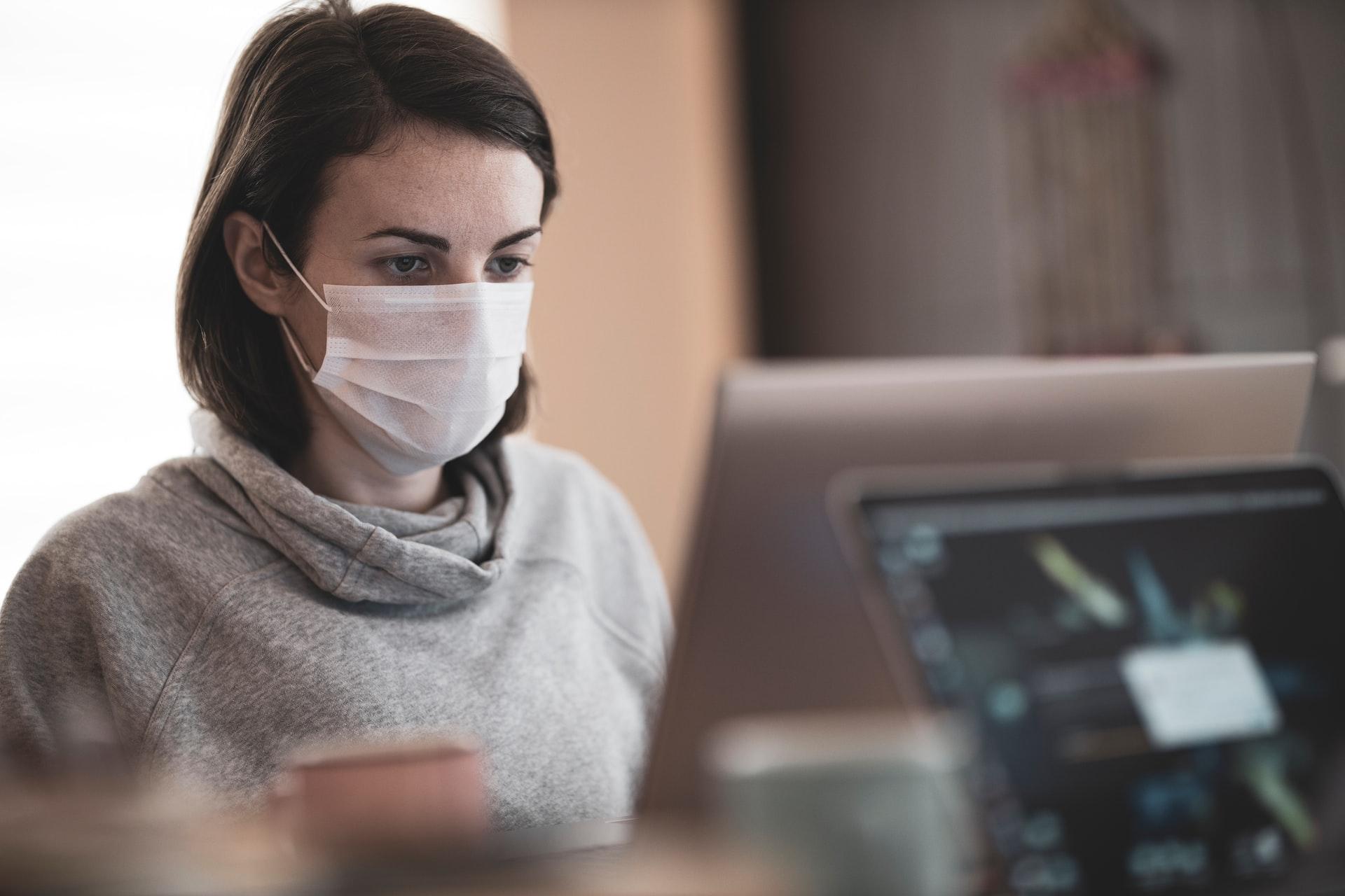 Le relazioni digitali migliorate dalla quarantena: una donna davanti al pc con la mascherina.