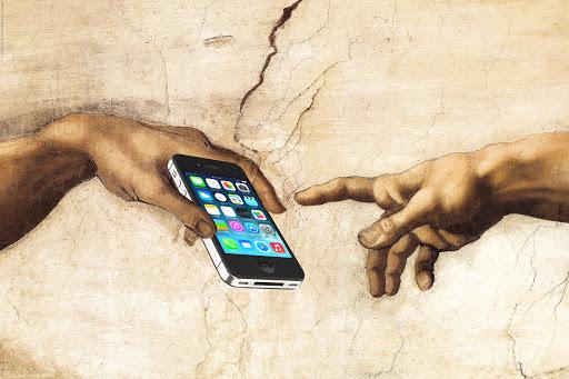 Svolta digitale: il particolare del tocco della Creazione di Adamo di Michelangelo, ma con il dito che tocca uno smartphone