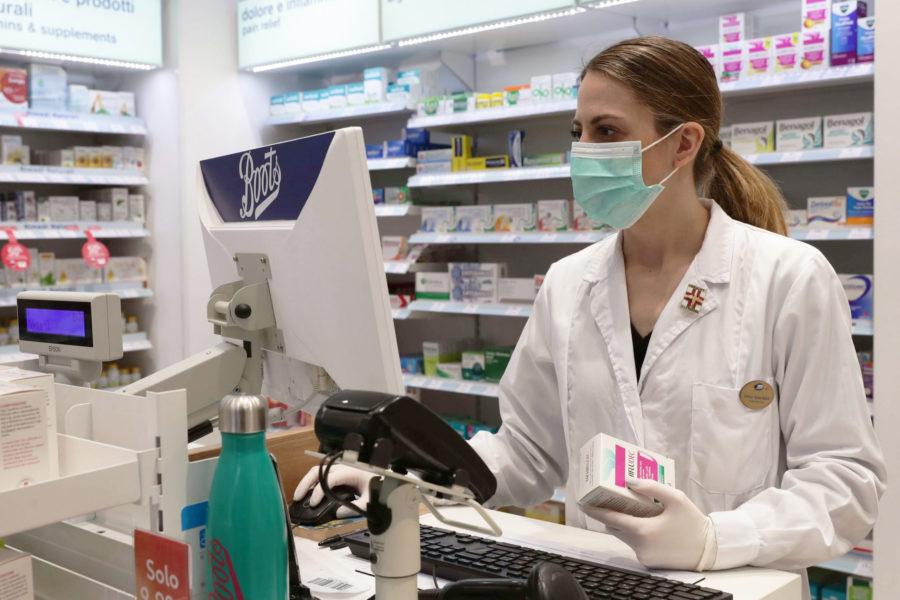 Farmacisti dipendenti al lavoro: una farmacista in mascherina al bancone
