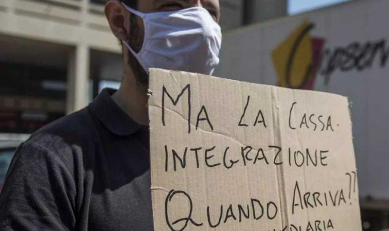 Cassa integrazione: un operaio con un cartello che chiede quando verrà erogata