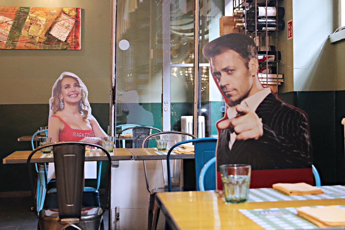 Fantasia nella riapertura dei ristoranti: l'idea del Consorzio Stoppani di Milano, con i cartonati di personaggi famosi al posto dei coperti inutilizzabili.