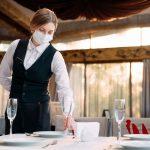 Ristorazione a Milano: una cameriera apparecchia un tavolo in mascherina in un ristorante di Milano