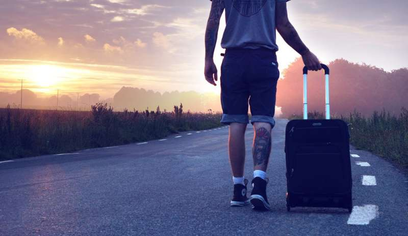 Giovane all'estero: un ragazzo su una strada con un trolley
