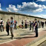 Uomini e donne di fronte a un confine delimitato da un muro.