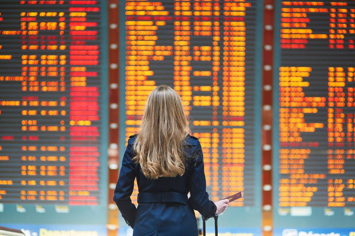 Cancellazione voli: una viaggiatrice di fronte a un tabellone pieno di voli cancellati