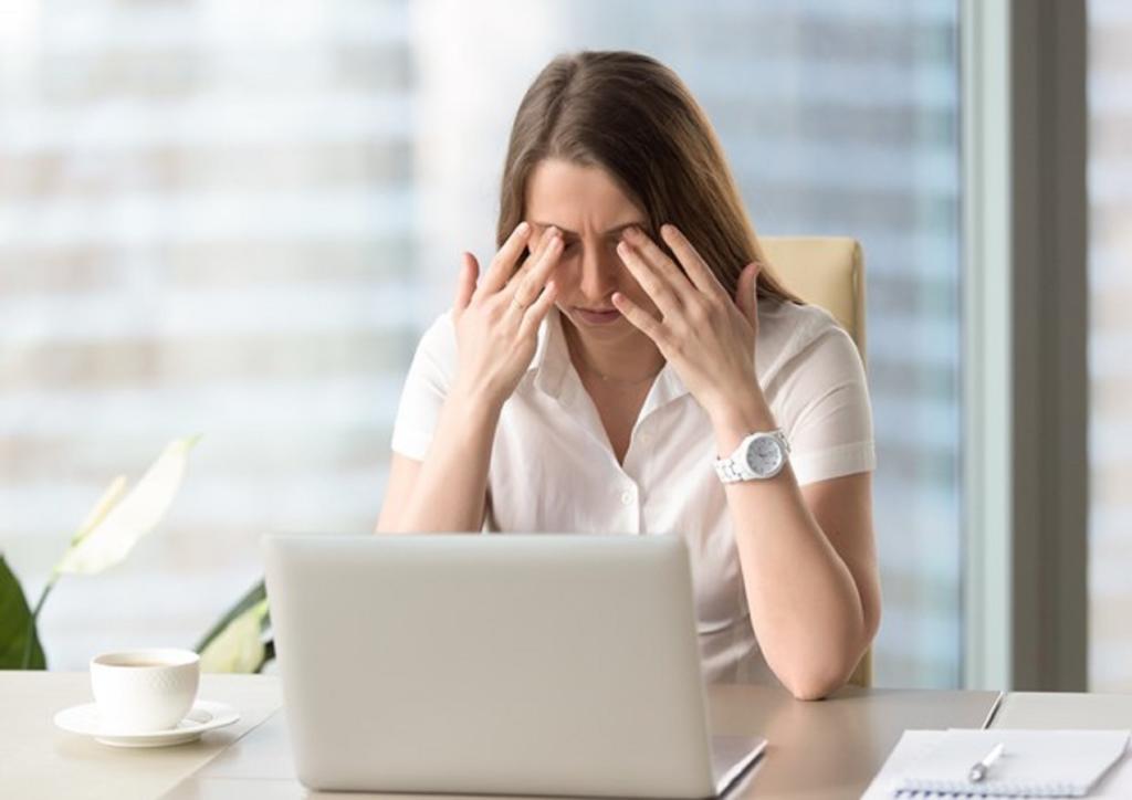Smart working femminile: una donna esausta con le mani sul viso davanti a un pc