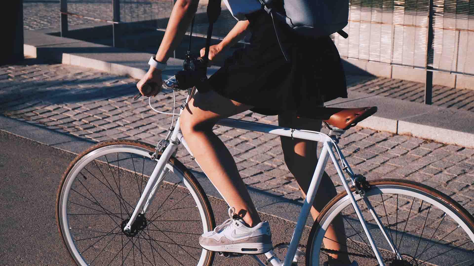 Mobilità dolce: una studentessa con lo zaino va a scuola in bici