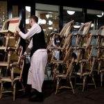 Un cameriere impila le sedie per chiudere un ristorante - forse per sempre.