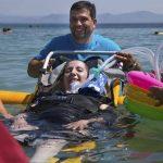 Turismo accessibile: un disabile fa il bagno sulla spiaggia di Maladroxia con respiratore e operatori specializzati.