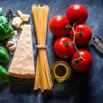 Agromafie: una pistola con dei prodotti agricoli (basilico, parmigiano, spaghetti, pomodori)